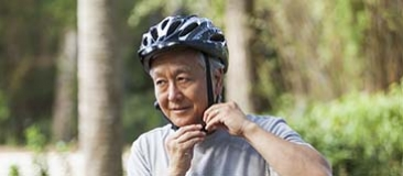 Older man putting on a bike helmet
