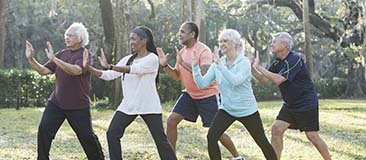 Group of older adults doing tai chi in the park