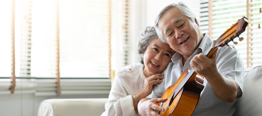 Older Asian man at home, playing guitar for his wife.