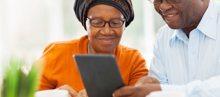Couple looking at dementia resources on a digital tablet