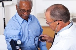 older man getting blood pressure checked by doctor