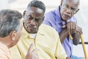 older African American man glaring at another man as a third man looks on