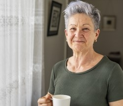 woman with Alzheimer's or a related dementia standing by window with coffee cup