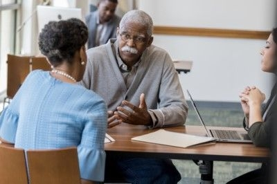 man with dementia talking with his daughter and an advisor