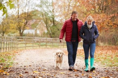 Midlife couple walking with dog