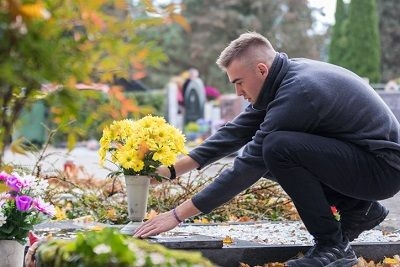 young man placing flowers by a loved one's grave