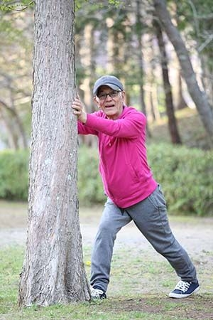 older man stretching against a tree