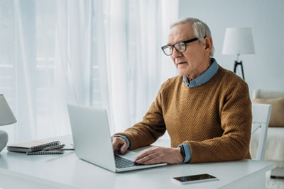 Older man sitting at a desk typing on a laptop