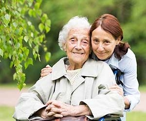 daughter lovingly holding mother with dementia