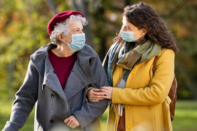 older woman with caregiver, both wearing face masks, walking in the park