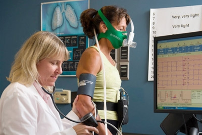 Researcher measuring breathing, heart rate, and blood pressure of participant while walking on a treadmill, results appear on a computer screen.