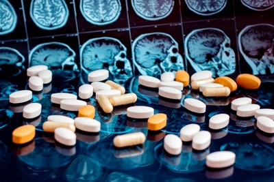 tablets and capsules of dementia prescription medications on a table with MRI images of a brain in the background