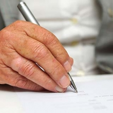 Older person's hand writing down health care directives