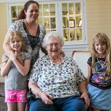 Older woman who is aging in place at home with her daughter and 2 granddaughters