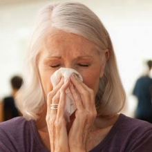 Older woman with a cold, blowing her nose