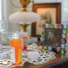 Medication bottles on a table by the bed of someone dying at home