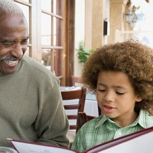 Older man with Alzheimer's looking at menus with grandson