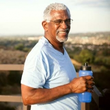 Older man drinking water in a park on a hot day