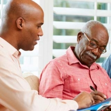 Older man getting help filling out legal and financial paperwork