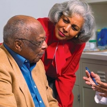 Older African-American couple discussion vaccinations with their doctor
