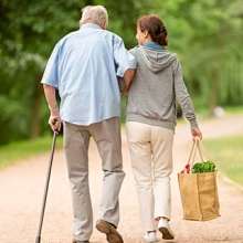 Older man with a cane walking with his caregiver from the grocery store