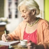 An older adult woman sitting a table in the kitchen writing in a notebook