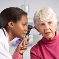 Doctor checking an older patient's ears