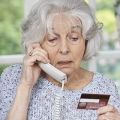 Older woman on the phone looking at her credit card