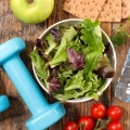 elements of a healthy lifestyle, including hand weights, fruits, and vegetables