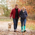 midlife couple walking dog