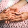 a pair of hands holding an elderly person's hand