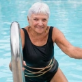 Older woman getting out of swimming pool