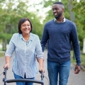 A community caregiver helping an older adult walk using a walker down a sidewalk in a park.