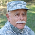Older male veteran soldier dressed in military fatigues sitting in a park.