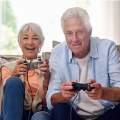 Older couple sitting on a couch in a living room, holding video game controllers, smiling, and playing a video game.