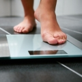 Bare feet shown on a weight scale in a bathroom.