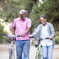 A happy older couple walking and pushing their bikes on a path in a park.
