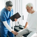 A physical therapist is examining the knee of an older man who is sitting on an exam table in a medical office.