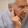 Older adult with hearing loss leaning in with his hand near his ear.