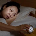 woman lying in bed reaching for an alarm clock.