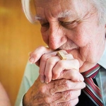 Older man with Alzheimer's kissing his wife's hand