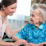 Older woman in a nursing home and her care aide