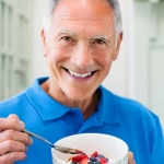 Older man eating a high fiber bowl of fruit