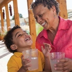 Grandmother drinking water with her grandson