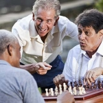 3 older men playing chess in the park