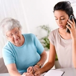 Younger woman helping her mother with paperwork and phone calls