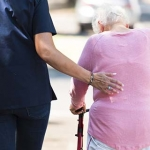 Professional caregiver helping an older woman using a walker