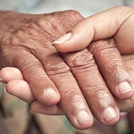 Close up of older adult and caregiver holding hands