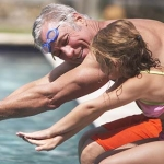 Grandfather teaching granddaughter to swim