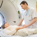 male medical technician with older woman about to get brain imaging test